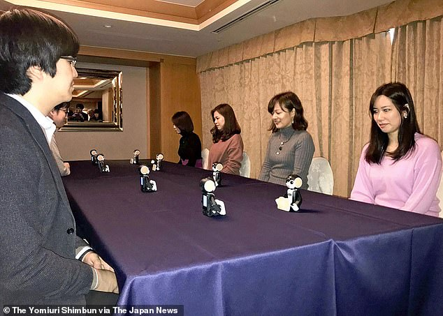 Young adults in Japan have discovered a new medium for finding a husband or wife - robots.At an event in Tokyo, men and women sat around a table with tiny bots between them