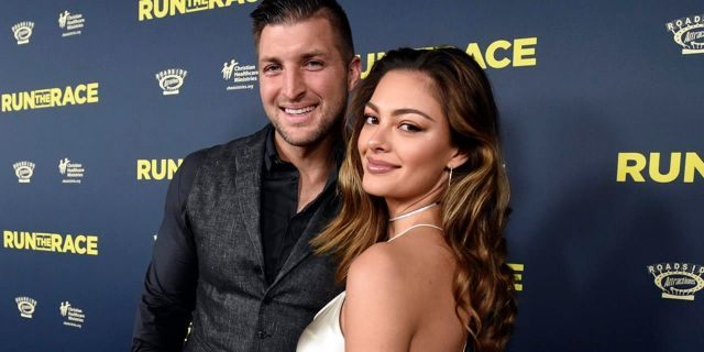 """Tim Tebow, left, and Demi-Leigh Nel-Peters attend the """"Run the Race"""" world premiere held at the Egyptian Theatre on Monday, Feb. 11, 2019, in Los Angeles. (Photo by Phil McCarten/Invision for RUN THE RACE, LLC/AP Images)"""