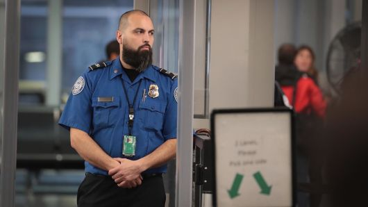 A Transportation Security Administration (TSA) worker screens passengers and airport employees at O