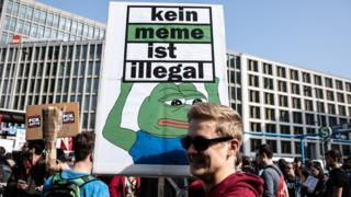 "A protestor holds a banner reading ""No meme is illegal"" during the ""Save The Internet"" demonstration in Berlin, Germany"