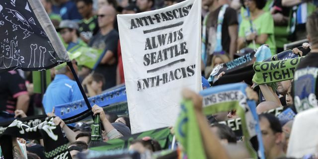 """Asign that reads """"Anti-Facist Always Seattle Anti-Racist"""" is displayed in the supporters section during an MLS soccer match between the Seattle Sounders and the Portland Timbers in Seattle, July 21, 2019. (Associated Press)"""