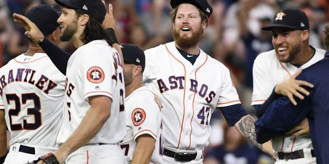 Houston Astros relief pitcher Chris Devenski, second from right, and teammates celebrate the team