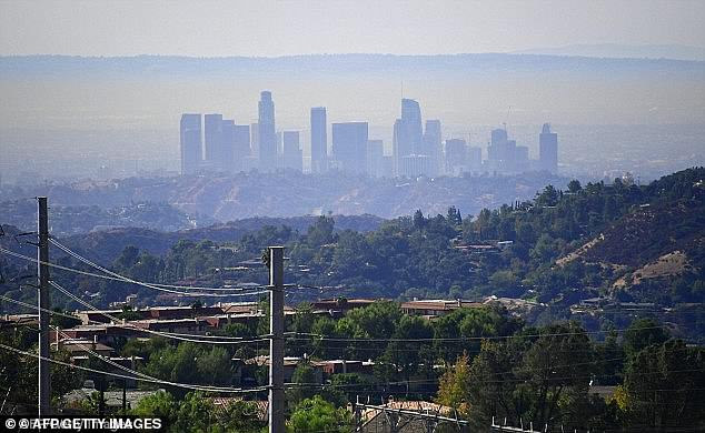 A new study from NYU Langone Health has found that visitors to highly polluted cities experience symptoms such as coughing and difficult breathing that took a week to recover from.Pictured: A layer of pollution hovers above Los Angeles, October 2017