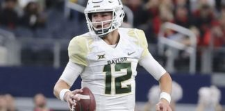 FILE - In this Nov. 24, 2018, file photo, Baylor quarterback Charlie Brewer scrambles out of the pocket before throwing a pass in the first half of an NCAA college football game against Texas Tech in Arlington, Texas. (Jerry Larson/Waco Tribune-Herald via AP, file)
