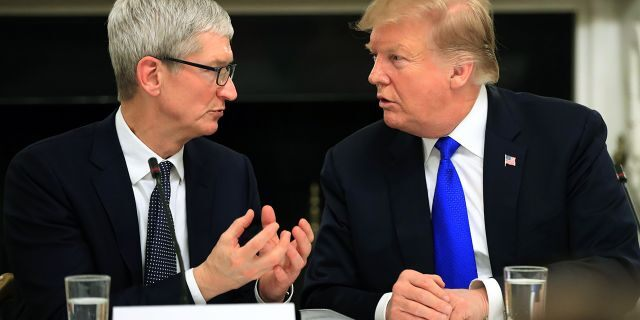File photo: President Donald Trump talks to Apple Inc. CEO Tim Cook during the American Workforce Policy Advisory Board