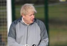 "British Prime Minister Boris Johnson puts on goalkeeping gloves before a girls"" soccer match during an election campaign event on December 7, 2019 in Cheadle Hulme, United Kingdom"