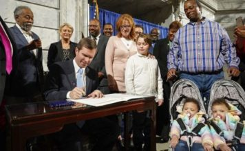 Kentucky Democratic Governor Andy Beshear signs an executive order to reinstate the voting rights of over 100,000 non-violent felons who have completed their sentences, at the Capitol in Frankfort, Ky., Thursday, Dec. 12, 2019. (AP Photo/Bryan Woolston)