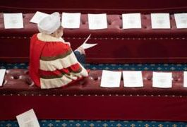A member of the House of Lords sits on a bench in the House of Lords