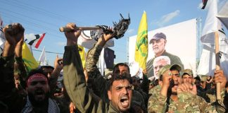 Anger: Iranian paramilitaries chant anti-US slogans during a protest over the killings of Iranian commander Qassem Soleimani and Iraqi paramilitary commander Abu Mahdi Al-Muhandis