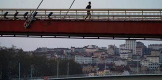 A man runs alone on an empty bridge in Lyon, central France, Saturday, March 21, 2020. French citizens are only allowed to leave their homes for necessary activities such as shopping for food, going to work or taking a quick walk due to the rapid spreading of the new coronavirus in the country.