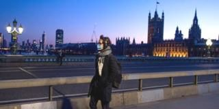 A man wearing a mask crosses Westminster Bridge past the Houses of Parliament