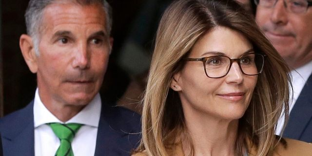 In this April 3, 2019, file photo, actress Lori Loughlin, front, and her husband, clothing designer Mossimo Giannulli, left, depart federal court in Boston after a hearing in a nationwide college admissions bribery scandal.