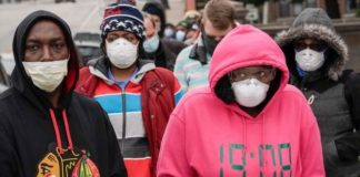 Voters masked against coronavirus line up at Riverside High School for Wisconsin