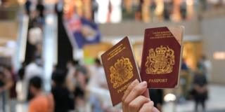 A pro-democracy demonstrator raises his British National Overseas (BNO) passports during a protest against new national security legislation in Hong Kong, China June 1, 2020.