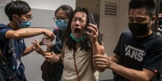 A woman reacts after she was hit with pepper spray deployed by police as they cleared a street with protesters rallying against a new national security law in Hong Kong