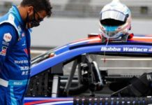 Bubba Wallace stands next to his car during a prayer before a NASCAR Cup Series auto race at Indianapolis Motor Speedway in Indianapolis.