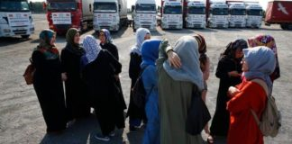FILE - In this Sept. 10, 2018 file photo, members of a Turkish pro-government aid group, wait for the departure of trucks carrying humanitarian aid destined for Idlib, Syria, in Istanbul. (AP Photo/Lefteris Pitarakis, File)