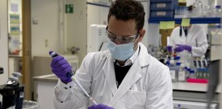 Johnson & Johnson plans to start its late-stage trial for its experimental coronavirus vaccine in September with up 60,000 people. Pictured: A lab technician fills a test tube during research on coronavirus at Johnson & Johnson subsidiary Janssen Pharmaceutical in Beerse, Belgium, June 17