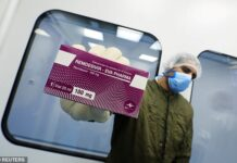 Gilead Sciences says it has ramped up production its antiviral, remdesivir, by 50-fold since January. Pictured: A laboratory technician holds a box of remdesivir at Eva Pharma Facility in Cairo, Egypt, June 25