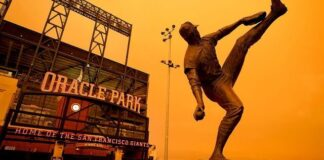 Wildfire smoke darkens the sky over a statue of former San Francisco Giants pitcher Juan Marichal outside Oracle Park before a baseball game between the Giants and the Seattle Mariners on Wednesday, Sept. 9, 2020, in San Francisco. (AP Photo/Tony Avelar)
