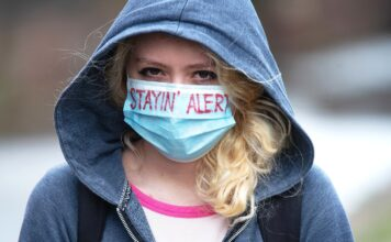 """Young woman wearing a face mask with the words """"stayin"""