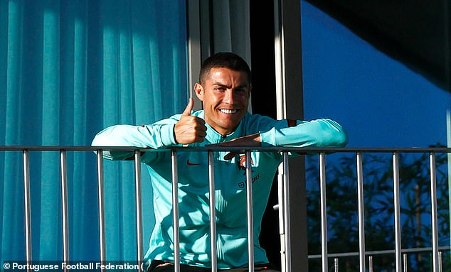 Cristiano Ronaldo has his thumbs up as he watches his team-mates train on Tuesday evening