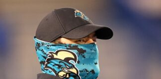 Questions have risen about the validity of a University of Georgia study that found neck gaiters are protective. Pictured:A member of the Coastal Carolina Chanticleers football team wears a neck gaiter at a football game, September 12