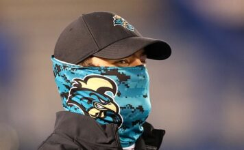 Questions have risen about the validity of a University of Georgia study that found neck gaiters are protective. Pictured: A member of the Coastal Carolina Chanticleers football team wears a neck gaiter at a football game, September 12
