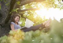 A woman working on a laptop sits in the branches of a tree, barefoot, surrounded by greenery illuminated by the summer sun