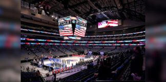 The Dallas Mavericks and Atlanta Hawks, along with a limited fan attendance, stand during the playing of the national anthem before the first half of an NBA basketball game in Dallas, Wednesday, Feb. 10, 2021.