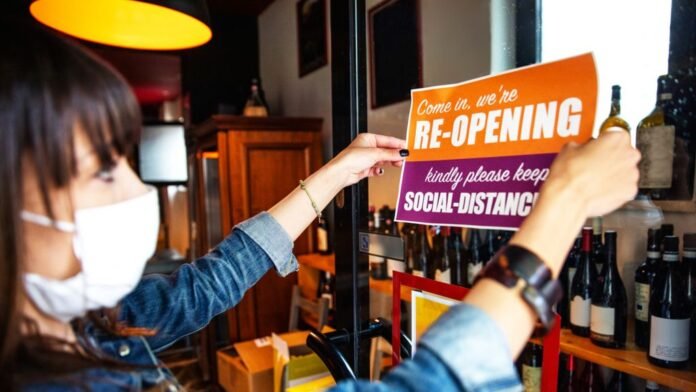 Woman puts a reopening sign up in a bar