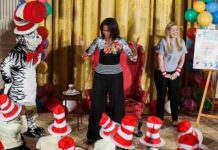 First Lady Michelle Obama dances with local students in the East Room of the White House after reading them Dr. Seuss