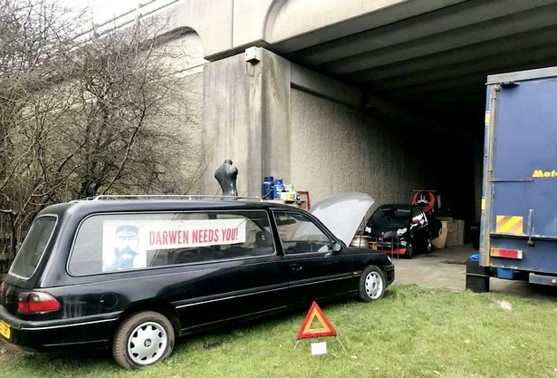 A funeral hearse has been parked by a road