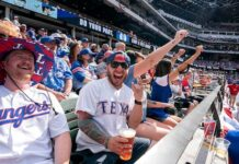 Texas Rangers fans Cameron Leverett, left, and Anthony Sosa celebrate during the fourth inning of a baseball game against the Toronto Blue Jays Monday, April 5, 2021, in Arlington, Texas. (AP Photo/Jeffrey McWhorter)