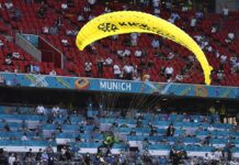 Spectators, officials and journalists take evasive action as the paraglider skims inches over their heads during his botched stunt at the Germany-France game in Munich last night