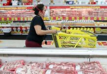 FILE - In this April 29, 2020 file photo, a shopper wears a mask as she walks through the meat products at a grocery store in Dallas, Wednesday. Wholesale prices, boosted by rising food costs, increased 0.8% in May 2021, and are up by a record amount over the past year, another indication that inflation pressures are rising since the economy has begun to re-open following the pandemic lockdowns. (AP Photo/LM Otero)