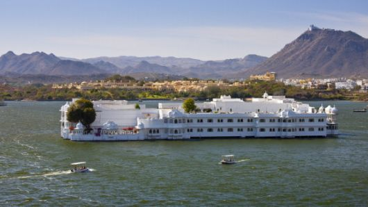 The Lake Palace Hotel with tourist boats arriving and leaving in Udaipur, Rajasthan, India.
