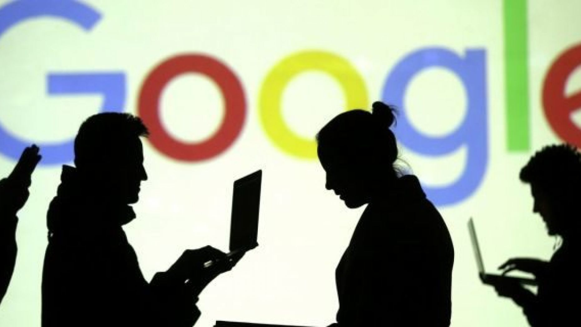 Silhouettes of laptop and mobile device users are seen next to a screen projection of Google logo in this picture illustration taken March 28, 2018.