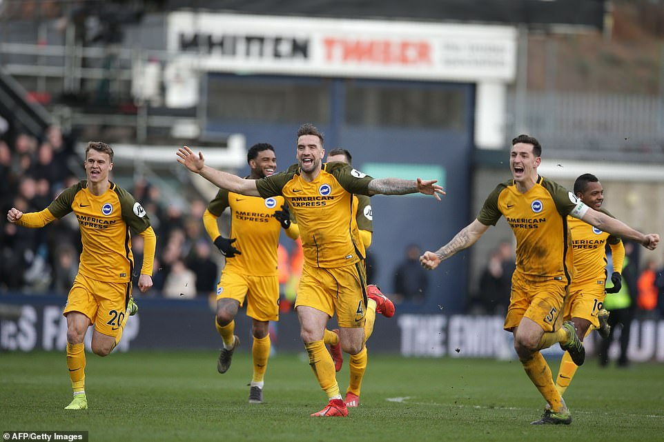 Brighton players celebrate after Millwall defender Jake Cooper misses his sudden death penalty in the FA Cup quarter-final