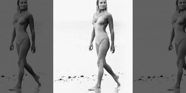 "Actress Bo Derek, with her hair in cornrows, walks along the beach in swimwear as Samantha Taylor in the 1979 movie ""10,"" directed by Blake Edwards."