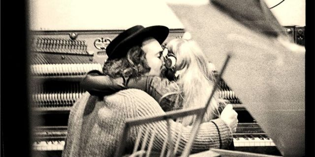David Crosby holding Joni Mitchell while both are seated at an upright piano, seen from the back, through the control room window at the recording studio. — Getty