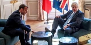 Boris Johnson places his right foot on a table at the Elysee Palace