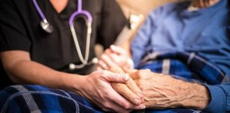 Nurse holds hand of patient at home