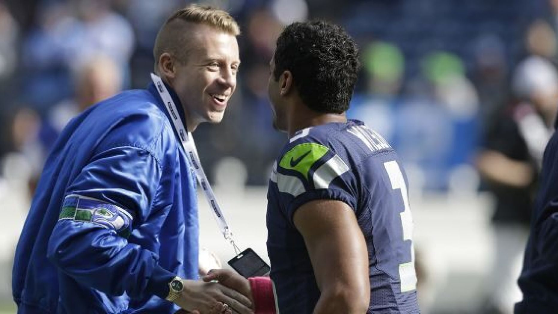 FILE - In this Oct. 13, 2013, file photo, Seattle hip hop and rap singer Macklemore, left, greets Seattle Seahawks quarterback Russell Wilson before an NFL football game between the Seahawks and Tennessee Titans in Seattle. The MLS soccer Seattle Sounders team announced Tuesday, Aug. 13, 2019, that they are adding Macklemore and Wilson to club