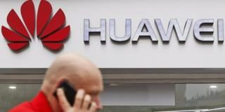 Man walks in front of a Huawei sign