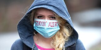 "Young woman wearing a face mask with the words ""stayin"