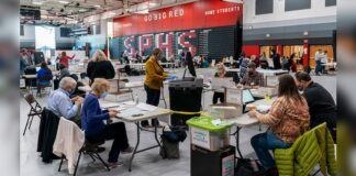 .MADISON, WI - NOVEMBER 03: Poll worker Rebecca Brandt, center, feeds a voting tabulation machine with absentee ballots in the gym at Sun Prairie High School on November 3, 2020 in Sun Prairie, Wisconsin. The entire gym was dedicated to counting the absentee ballots (Photo by Andy Manis/Getty Images)