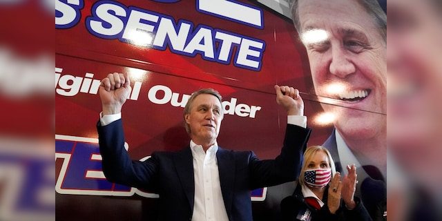 Republican candidate for Senate Sen. David Perdue and his wife Bonnie reacts during a campaign stop at Peachtree Dekalb Airport Monday, Nov. 2, 2020, in Atlanta. (AP Photo/John Bazemore)
