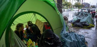 People try to stay warm as they face the elements inside a homeless encampment flooded under a rainstorm across the Echo Park Lake in Los Angeles, March 12, 2020. (Associated Press)