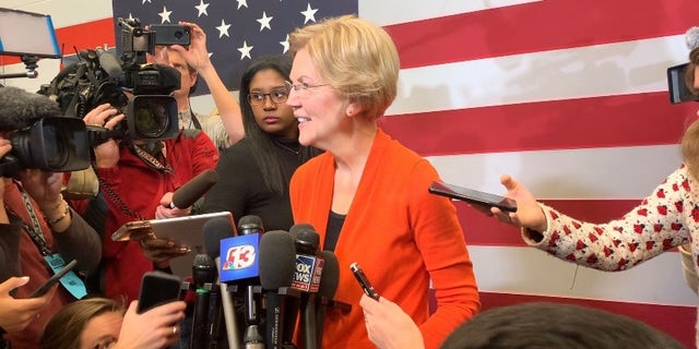 """Democratic presidential candidate Sen. Elizabeth Warren speaks with reporters while campaigning in Marshalltown, Iowa on Jan. 12, 2019. Warren comes out with a new book, """"Persist"""" on May 4, 2021."""
